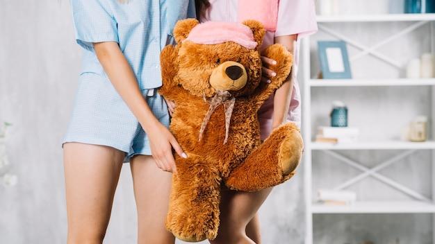 Vista de la sección media de dos amigas sosteniendo un juguete suave Foto gratis