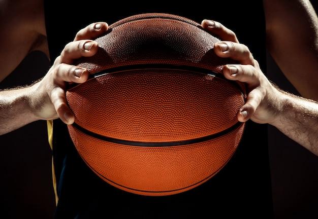Vista de la silueta de un jugador de baloncesto con baloncesto en la pared negra Foto gratis