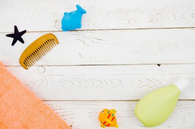Vista superior de accesorios de baño para bebés con fondo de madera Foto gratis