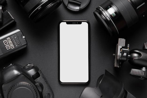 Vista superior de los accesorios de la cámara y el teléfono inteligente sobre fondo negro Foto gratis