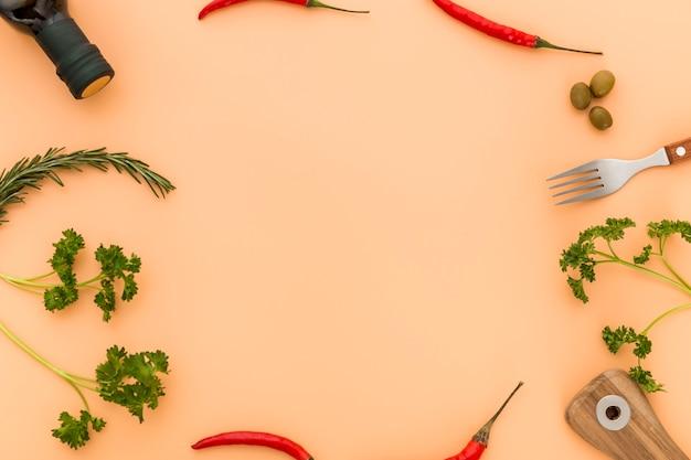 Vista superior de aceite de oliva y pimientos con cubiertos Foto gratis