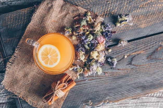 Vista superior de agua de color naranja en la taza con limón y té en tela de saco y fondo de madera oscura. horizontal Foto gratis
