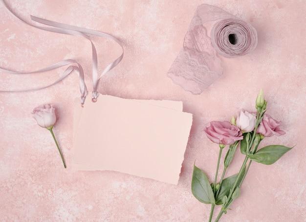 Vista superior arreglo de boda con invitación y flores. Foto gratis