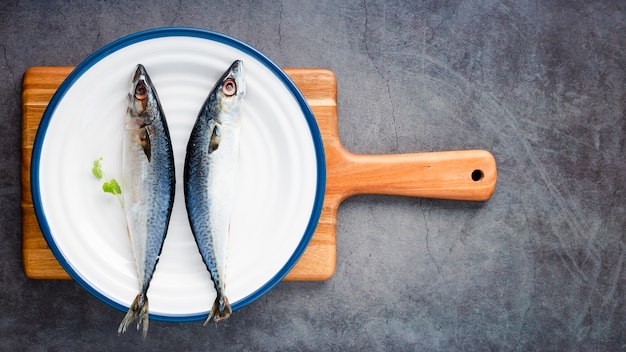 Vista superior arreglo con pescado en tabla de cortar Foto gratis