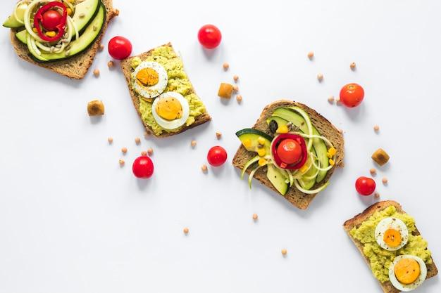 Vista superior de un bocadillo saludable con huevo cocido y aguacate en rodajas Foto gratis