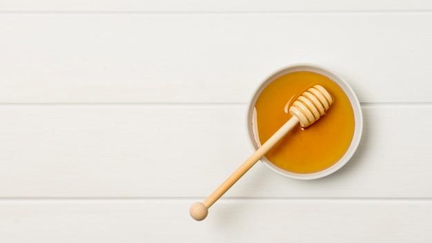 Vista superior bol de miel con cuchara Foto gratis