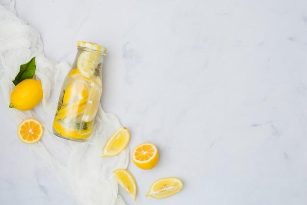 Vista superior botella de limonada con limones Foto gratis