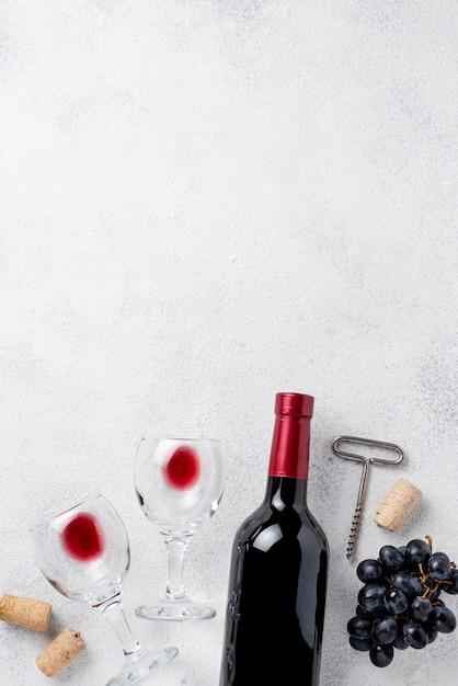 Vista superior botella de vino tinto y copas Foto gratis