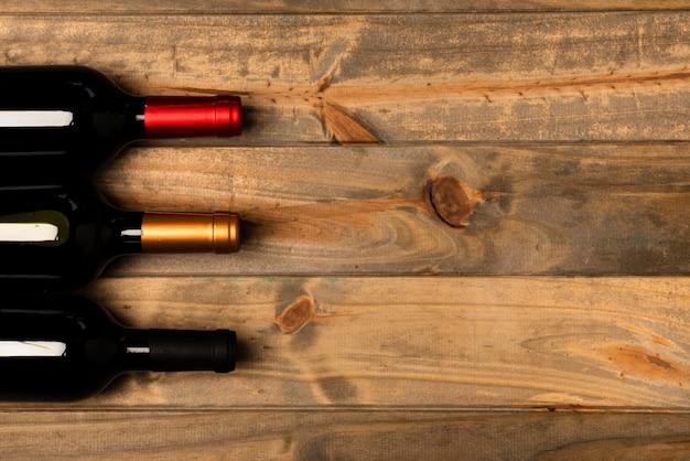 Vista superior de botellas de vino con fondo de madera Foto gratis
