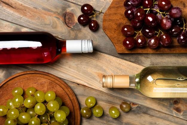 Vista superior de botellas de vino con uvas Foto gratis