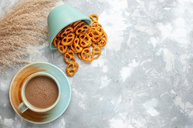 Vista superior de café con leche con galletas en el fondo claro bebida crujiente café en color Foto gratis