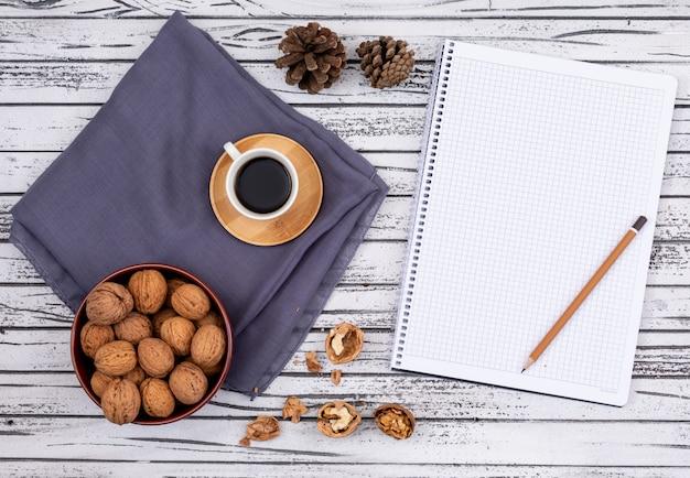 Vista superior de café con nueces y copia espacio en el cuaderno sobre fondo blanco de madera horizontal Foto gratis