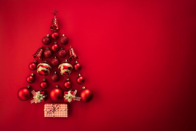 Vista superior de la caja de regalo con la bola roja y la campana en la forma del árbol de navidad en fondo rojo. Foto Premium