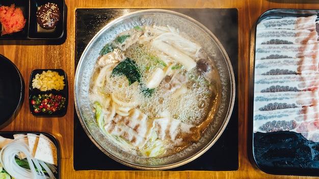 Vista superior del caldo shabu caliente e hirviendo con col, eryngii, enotitake, tofu y cerdo kurobuta Foto Premium