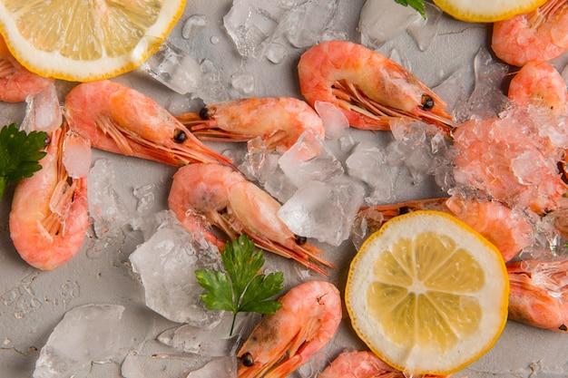 Vista superior de camarones sobre hielo con rodajas de limón Foto Premium