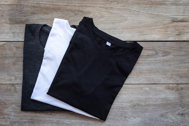 Vista superior de la camiseta de color sobre fondo de tablón de madera gris Foto Premium