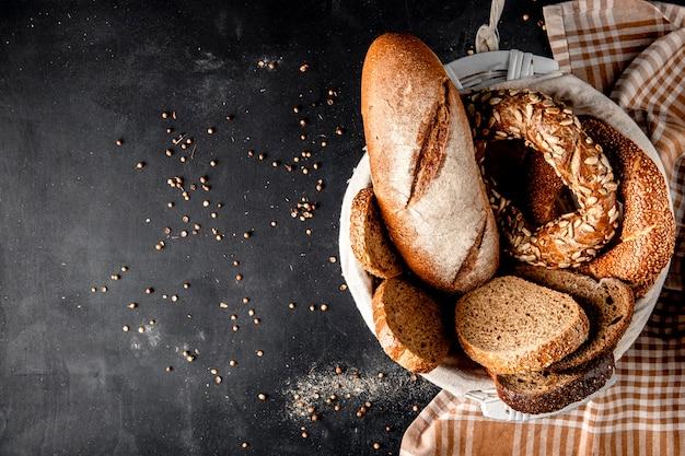 Vista superior de la canasta llena de panes como baguette bagel centeno con semillas de girasol en superficie negra Foto gratis