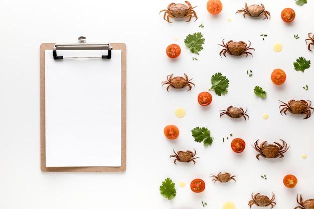 Vista superior de cangrejos y tomates con bloc de notas Foto gratis