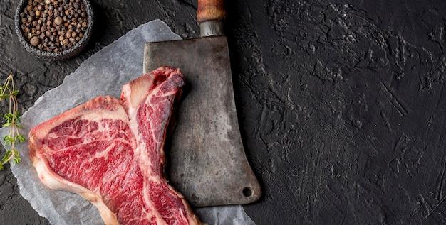 Vista superior de carne con especias y cuchilla Foto gratis