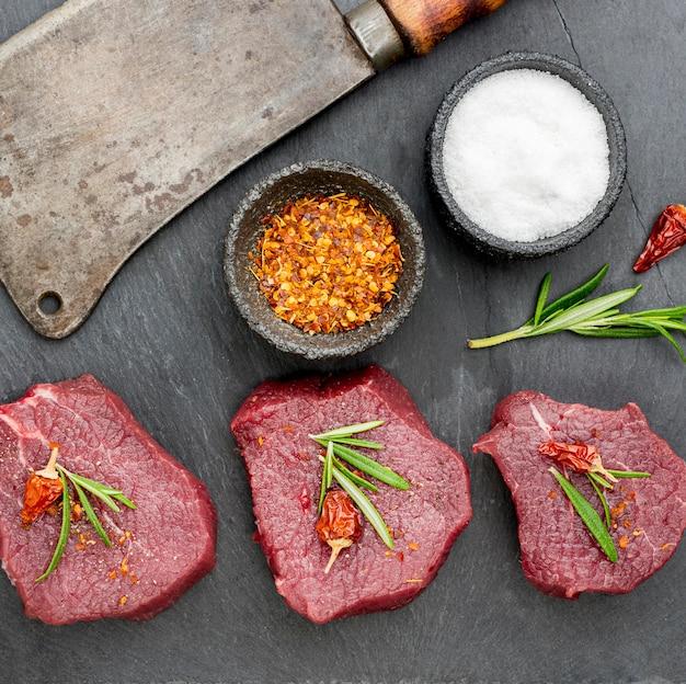 Vista superior de carne con especias y hierbas. Foto gratis