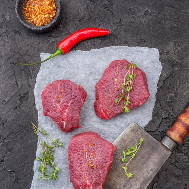 Vista superior de carne con hierbas y cuchilla Foto gratis