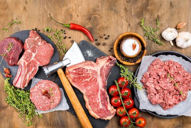 Vista superior de carne con hierbas y tomates. Foto gratis