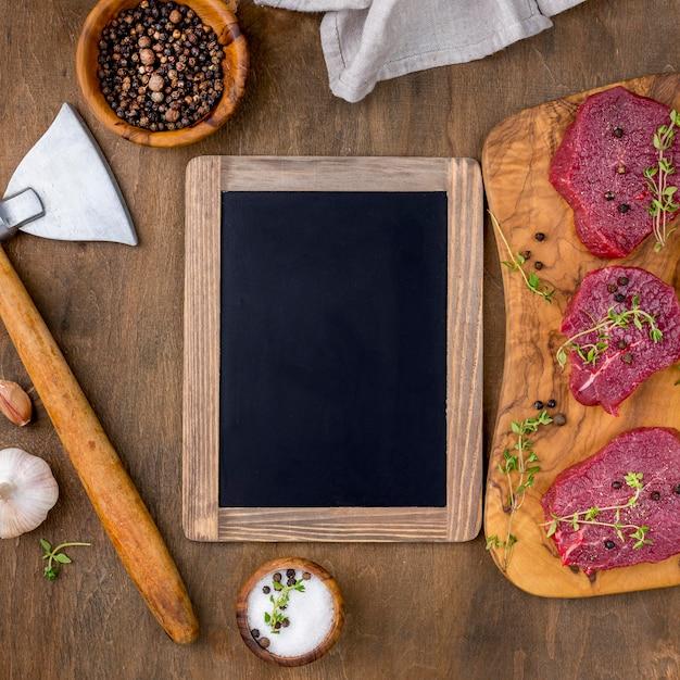 Vista superior de carne con pizarra Foto gratis
