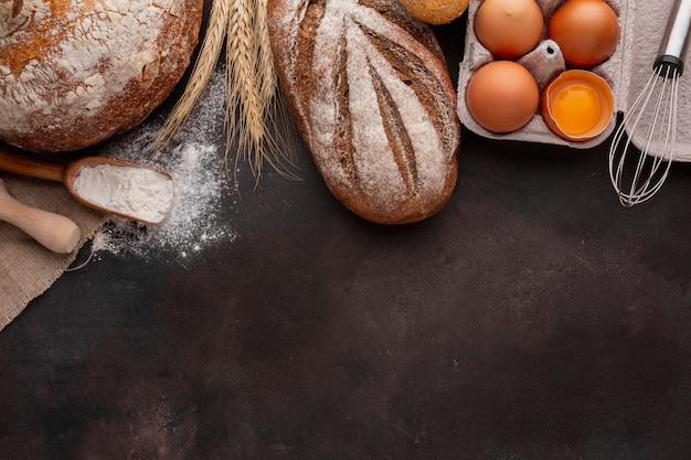 Vista superior de cartón de huevos y pan Foto gratis