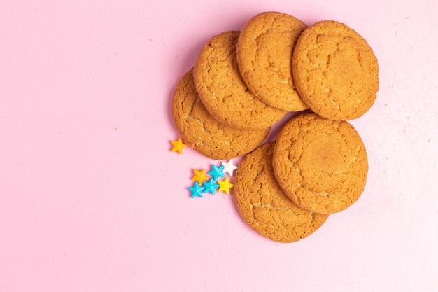 Vista superior cercana deliciosas galletas dulces horneadas forradas en el fondo rosa Foto gratis
