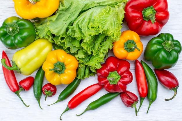 Vista superior cercana de ensalada verde junto con pimientos morrones y pimientos picantes en el escritorio blanco, ingrediente de comida vegetal Foto gratis