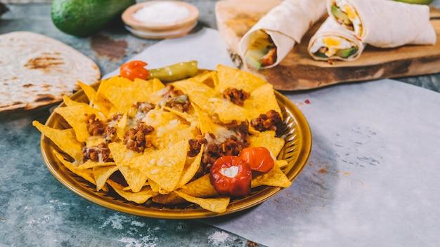 Vista superior de chips de tortilla mexicana de nachos en un tazón con tacos mexicanos en tabla de cortar Foto gratis