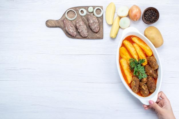 Vista superior de chuletas de carne cocida con salsa de patatas y verduras junto con carne cruda en el escritorio de luz, comida comida carne vegetal Foto gratis