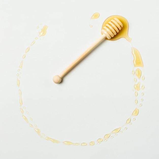 Vista superior círculo de miel con cuchara Foto gratis