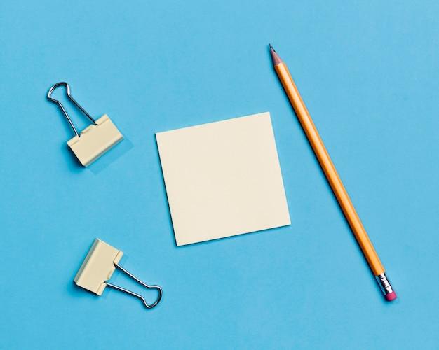 Vista superior de clips de papel y lápiz sobre el escritorio Foto gratis