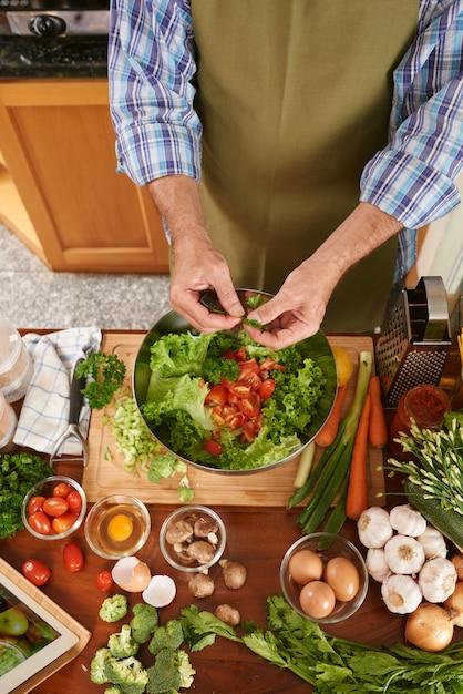 Vista superior del cocinero irreconocible que agrega perejil a la ensaladera Foto gratis