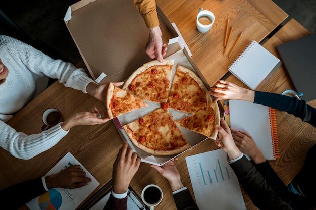 Vista superior de colegas comiendo pizza durante un descanso de la reunión de oficina Foto gratis
