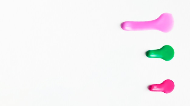Vista superior del color de esmalte de uñas de muestra aislado en superficie blanca Foto gratis