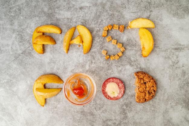 Vista superior de comida rápida escrita en la mesa Foto gratis