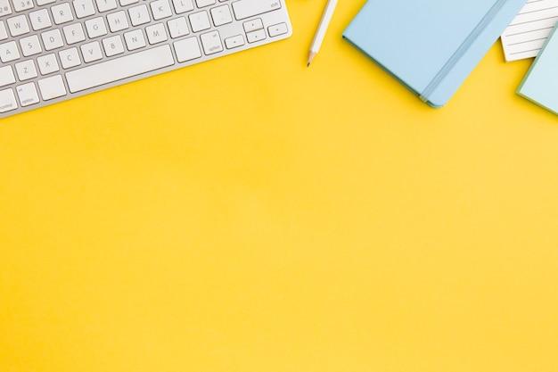 Vista superior composición del lugar de trabajo sobre fondo amarillo con espacio de copia Foto gratis