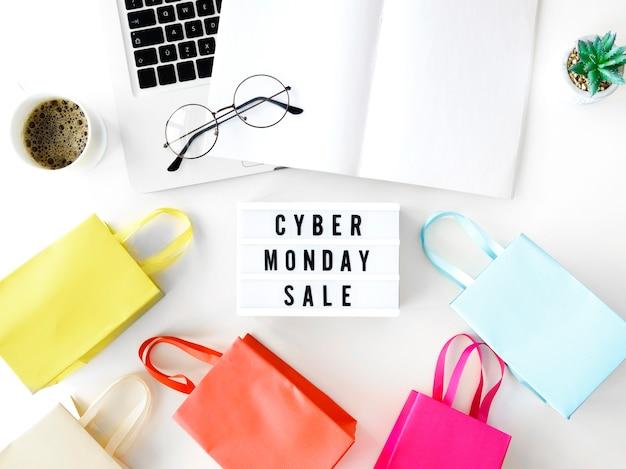 Vista superior de la computadora portátil cyber monday con bolsas de compras y caja de luz Foto gratis