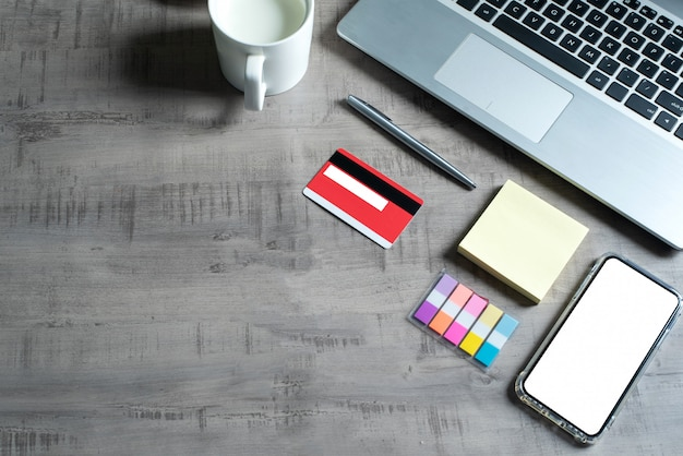 Vista superior de la computadora portátil, teléfono inteligente, tarjeta de crédito, taza de leche, nota de papel, bolígrafo, en una mesa de madera con negocios, comercio, finanzas, concepto de educación y diseño Foto Premium