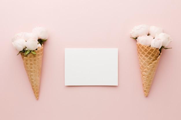 Vista superior del cono de helado floral con tarjeta vacía Foto gratis