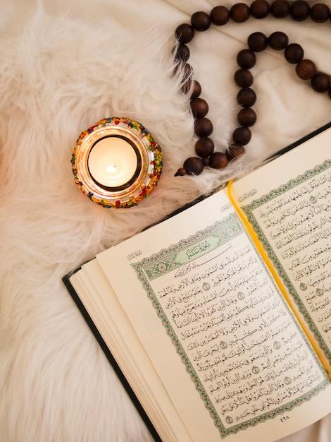 Vista superior del corán, cuentas de oración y una vela. Foto gratis