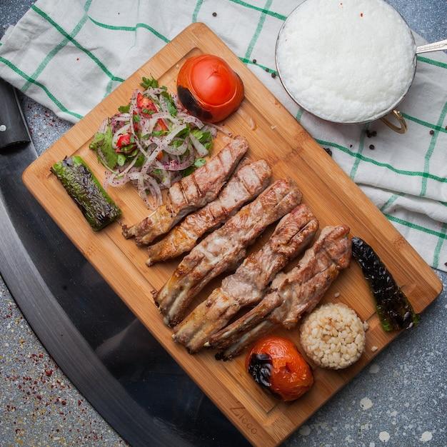 Vista superior costillas de kebab con verduras fritas y cebolla picada y ayran y cuchillo en tabla de cortar Foto gratis