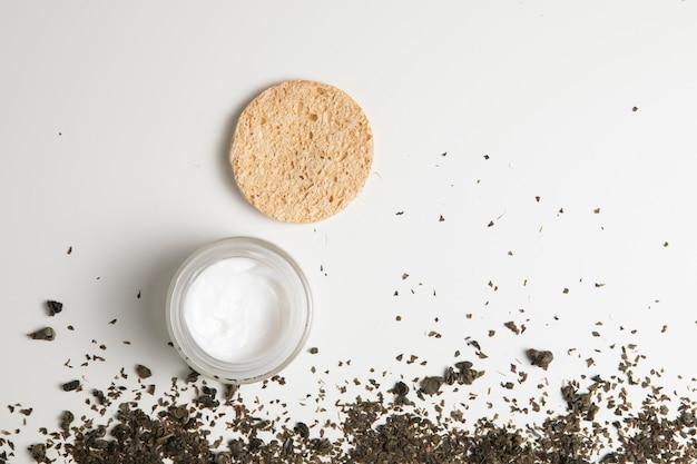 Vista superior de crema natural y hierbas sobre fondo blanco. Foto gratis