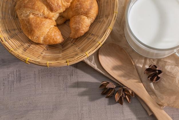 Vista superior de croissant en la cesta, una taza de leche, cuchara de madera Foto Premium