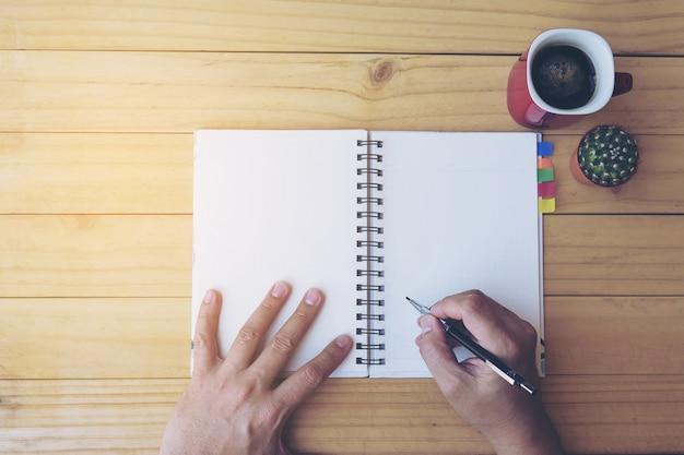 Vista superior del cuaderno de escritura de hombre en mesa de madera con taza de café y olla pequeña de cactus Foto gratis