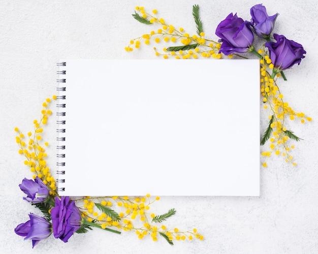 Vista superior cuaderno y flores de primavera Foto gratis
