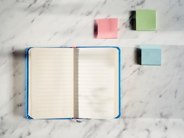 Vista superior del cuaderno con notas adhesivas Foto gratis