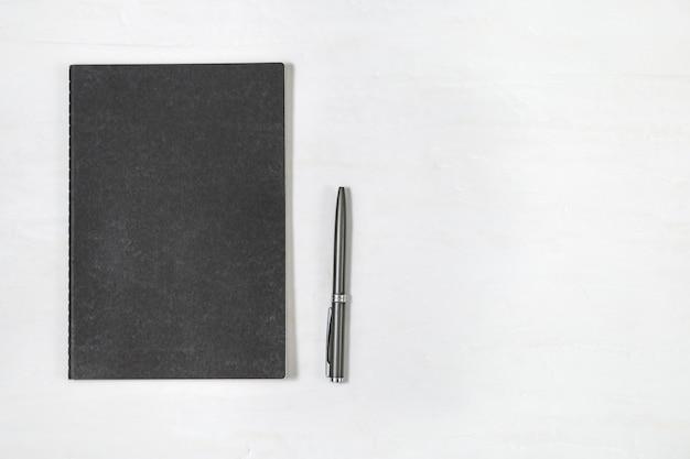Vista superior del cuaderno de tapa negra cerrada con lápiz brillante sobre fondo blanco de escritorio. mock up cuaderno. escritorio de oficina mínimo con papelería. Foto Premium